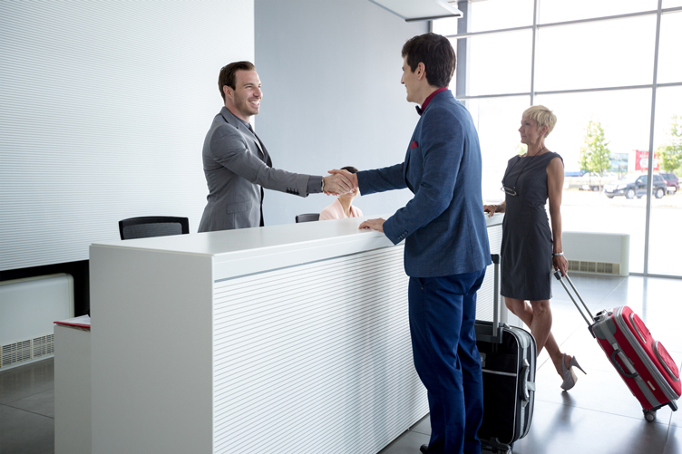 Concierge shaking hands with customer at front desk
